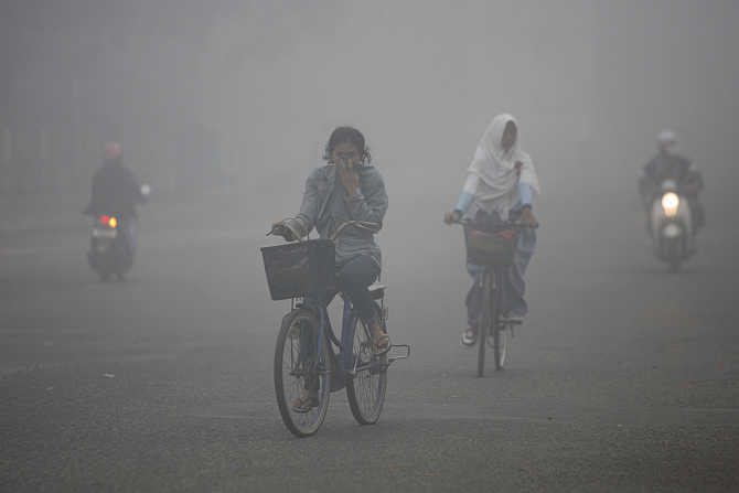 Residents cycle through the haze-blanketed town of Sampit, in Indonesia's Central Kalimantan province.