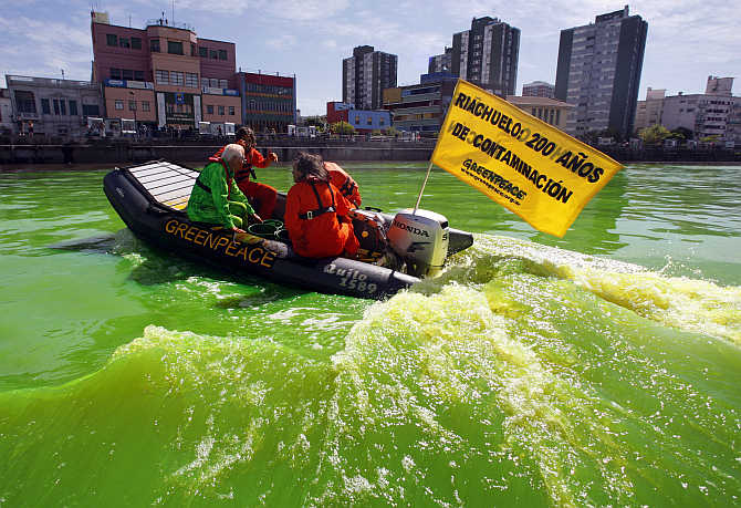 A boat with Greenpeace activists makes its way across the Matanza-Riachuelo river, Argentina's most polluted basin, after it was dyed green during a demonstration.
