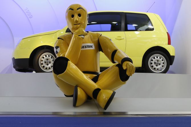 A model dressed as a crash-test dummy sits in front of a Volkswagen Lupo.