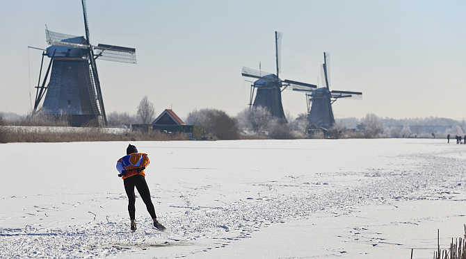 A lone skater skates past three windmills in Kinderdijk near Rotterdam, the Netherlands.