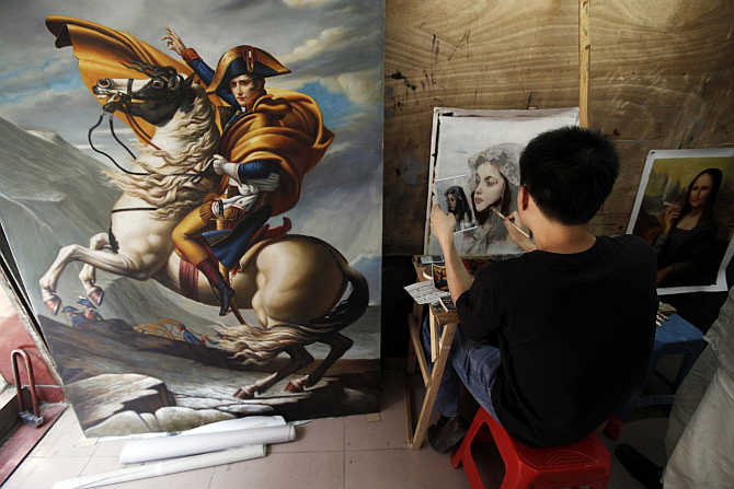 A painter works on a portrait in a studio at Dafen Oil Painting Village in Shenzhen, south China's Guangdong province.