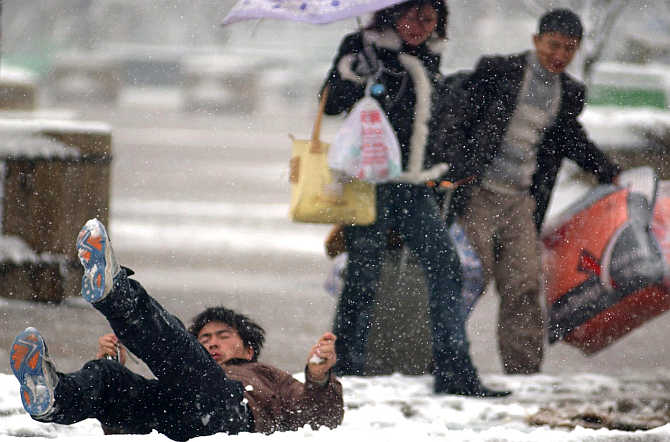 A man falls on a slippery road while on his way to the South Railway Station in Ningbo in east China's Zhejiang province.