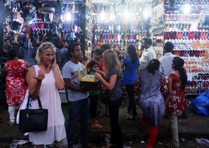 People shop from roadside stalls at a market in Mumbai.