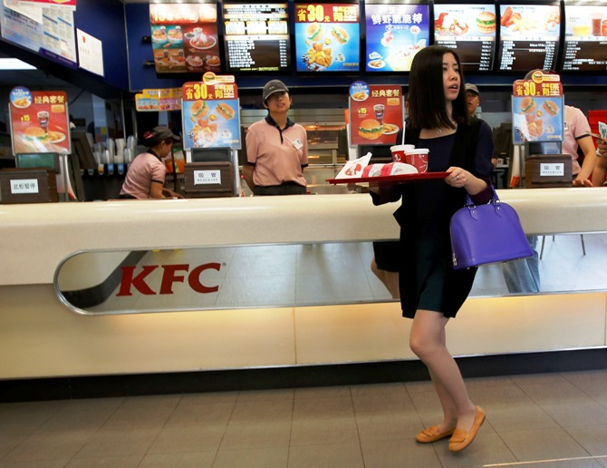 A woman holds food inside a KFC restaurant in Beijing.