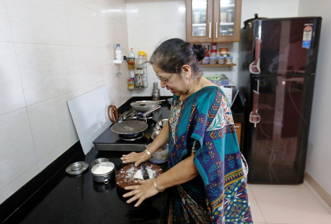 Rekha Chitre, 63, cooks in the kitchen of her flat at the Athashri retirement village in Baner, on the outskirts of Pune.