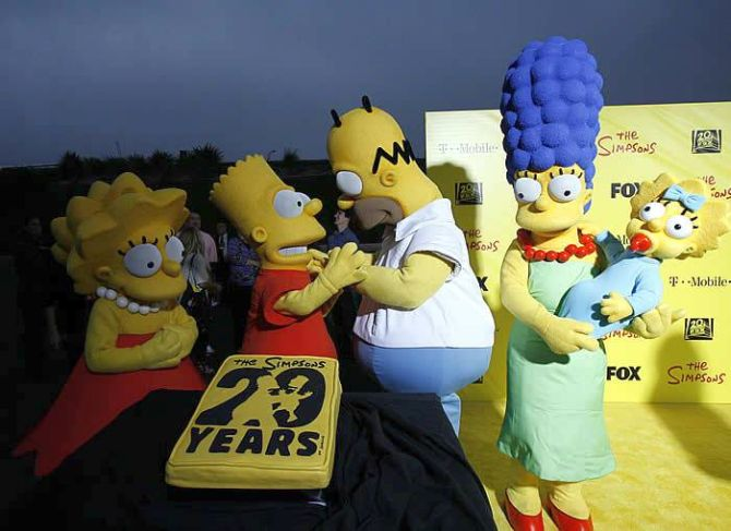 Characters (from L-R) Lisa, Bart, Homer, Marge and Maggie stand by a cake at the 20th anniversary party for the television series The Simpsons.