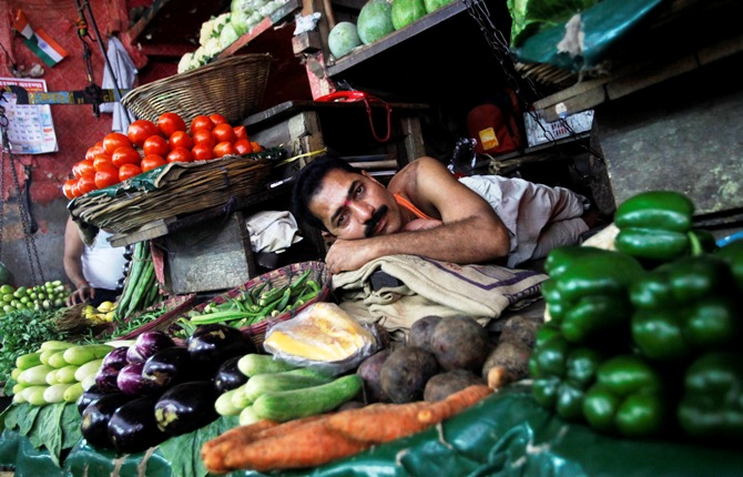 A vendor rests as he waits for customers at a vegetable market in Mumbai.