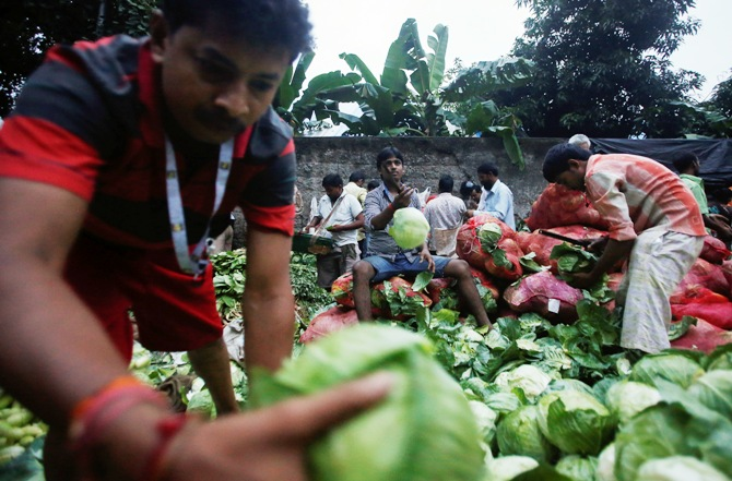 Vendors sort out cabbages along a road outside a wholesale vegetable market at dawn in Mumbai.