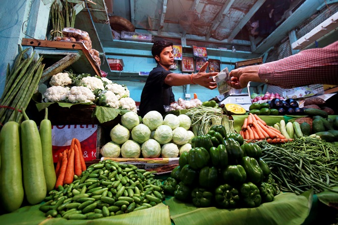 A vendor accepts money from a customer at his vegetable stall at a wholesale fruit and vegetable market in Mumbai.