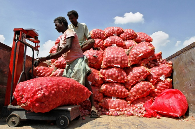A man weighs a sack of onions before unloading it from a supply truck at a wholesale market in Chennai.