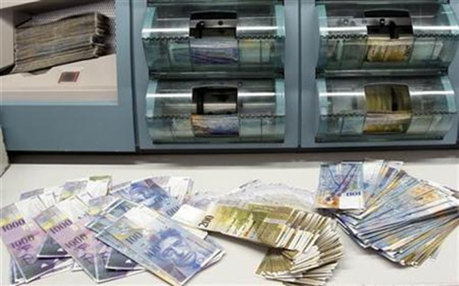 Swiss franc banknotes of several values are sorted in a money counter in a bank in Zurich.
