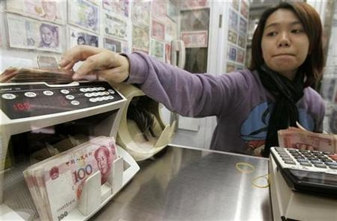 Yuan notes are counted at a currency exchange office in Hong Kong.