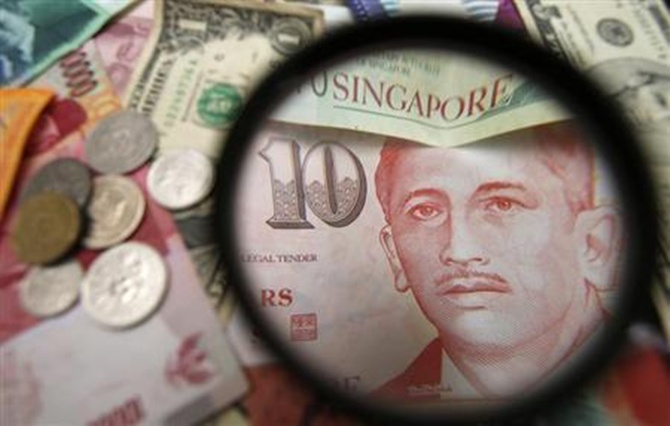 Singapore currency notes are seen through a magnifying glass among other currencies in this photo illustration taken in Singapore