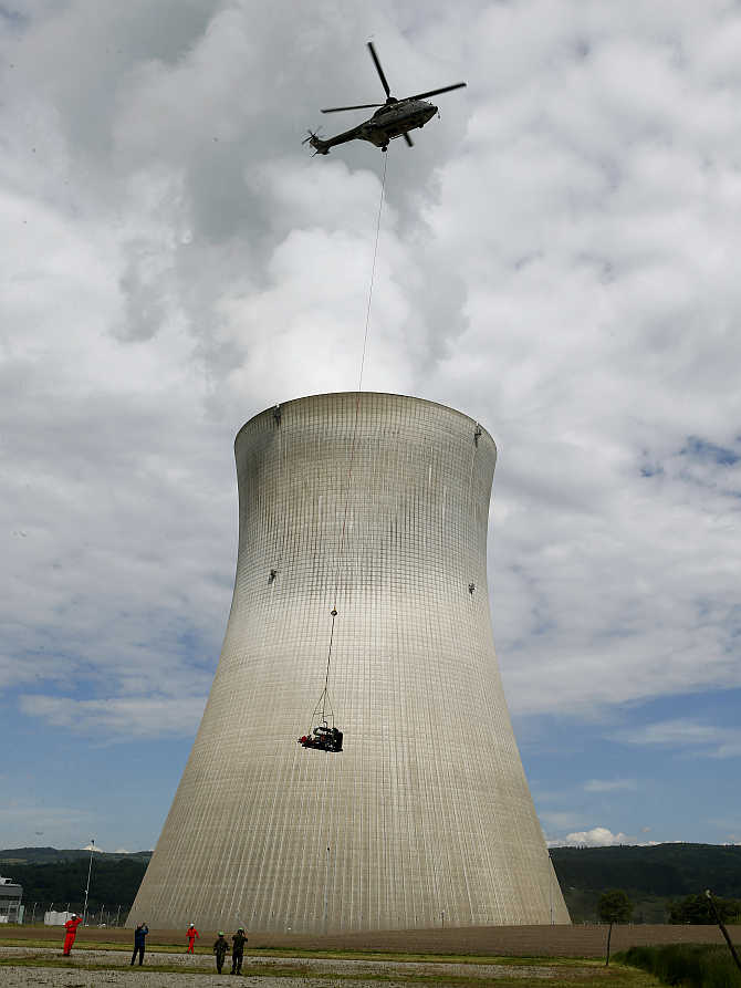 An air force helicopter transports a mobile water pump in front of the nuclear power plant near the northern Swiss town Leibstadt.