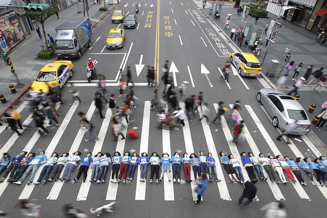 People lie on a pedestrian crossing during a flashmob event in a shopping area in Taipei, Taiwan.