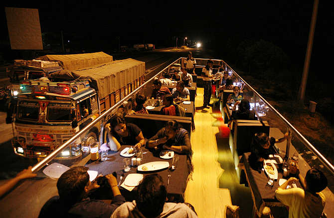 People dine on a double-decker bus which has been converted to a mobile restaurant as it travels through the streets of Ahmedabad.