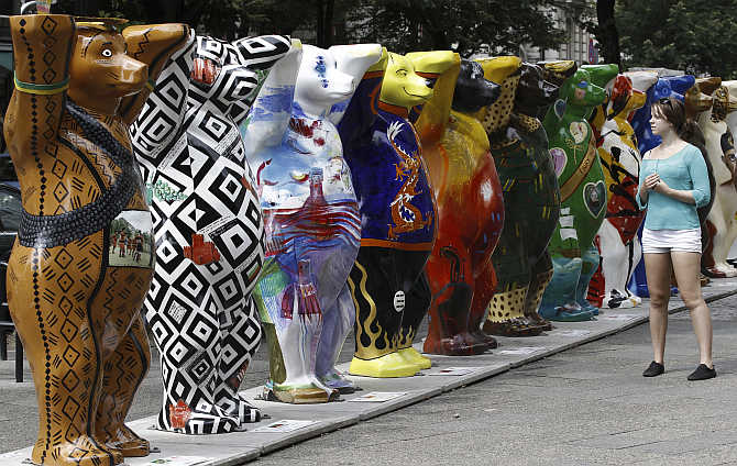 A woman looks at Buddy Bear sculptures at the Kurfuerstendamm boulevard in Berlin, Germany.