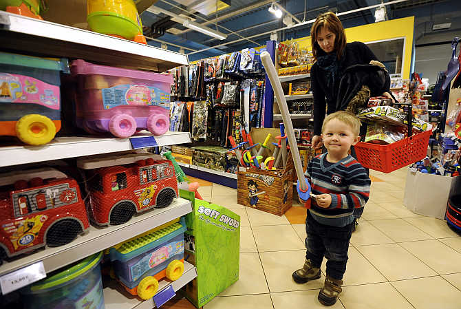 Jana Papulakova watches her two-year-old son Tobias play with a sword inside the Alltoys toy shop in Trencin, Slovakia.