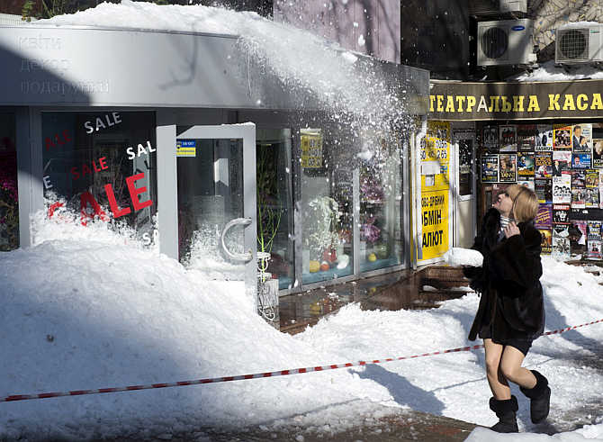 A woman walks on the street as snow falls from a roof after an unusually heavy snowstorm in Kiev, Ukraine.