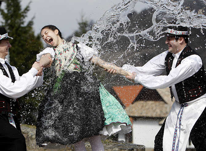Boys hold onto a girl as they throw water at her as part of traditional Easter celebrations during a media presentation in Holloko, 100km east of Budapest, Hungary.