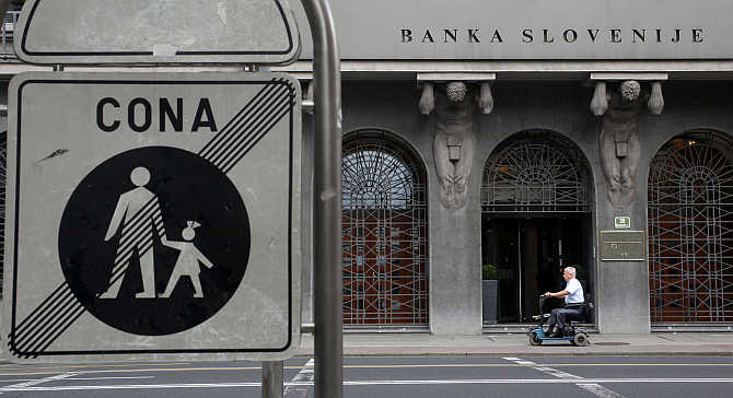 A man in a mobility scooter drives past Slovenia's National Bank in Ljubljana, Slovenia.