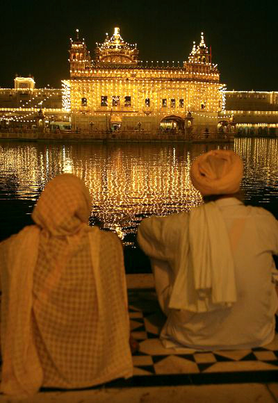 Devotees pay obeisance near the holy Sikh shrine of Golden Temple on the eve of Diwali festival in Amritsar.