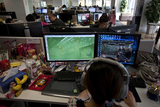 An employee watches a computer screen displaying the video game Glorious Mission Online at the game developer's office in Shanghai, China.
