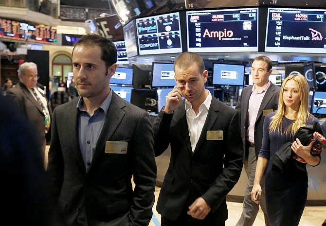 Twitter co-founders Evan Williams, left, and Jack Dorsey, centre, walk together during the Twitter's IPO on the floor of the New York Stock Exchange.