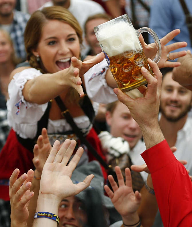 A visitor reaches for one of the first mugs after the opening ceremony of Oktoberfest in Munich, Germany.