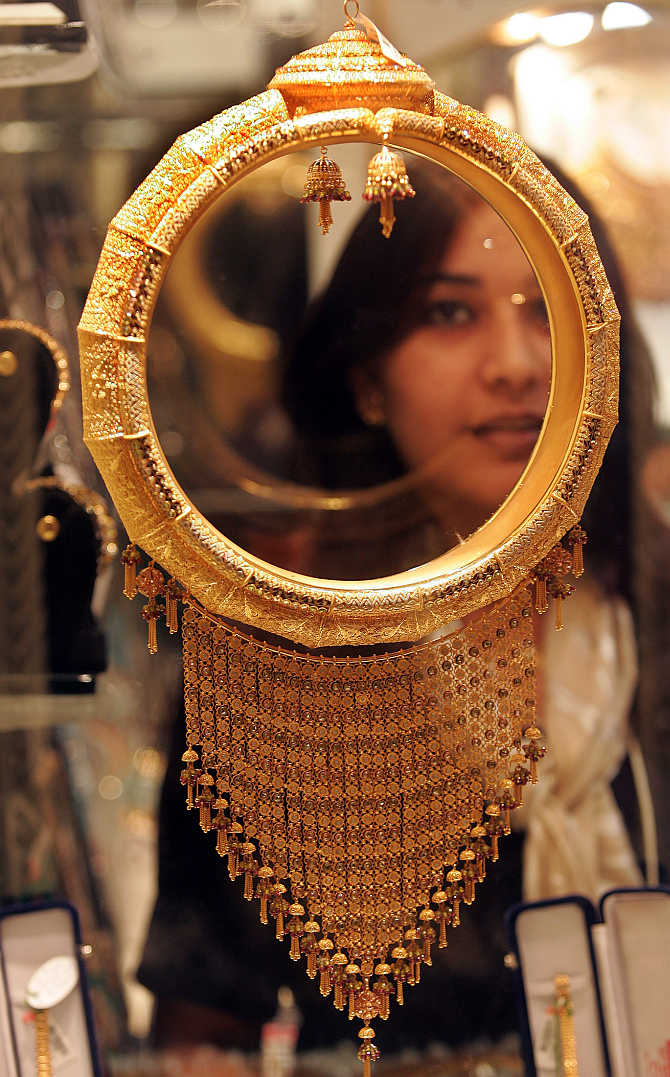 A woman looks at gold ornament in Kolkata.