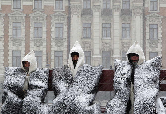 Balkar men, dressed in national clothes, sit during a heavy snowfall as they take part in a protest rally in central Moscow, Russia.