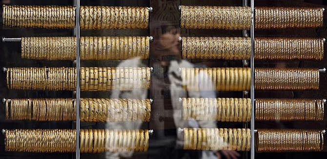 A woman is reflected on a window of a jewellery shop where gold bangles are on display in Istanbul, Turkey.