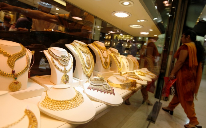 A woman walks past gold jewellery in a display window.