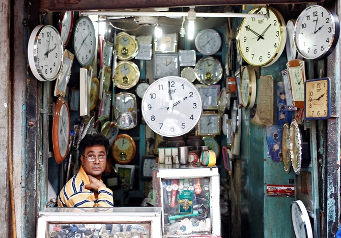 A shopkeeper waits for customers at his shop selling wall clocks in the old quarters of Delhi.