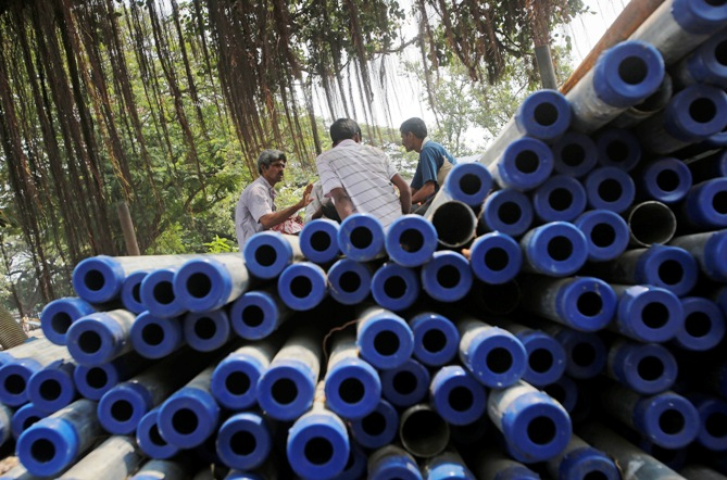 Workers sit on iron pipes before loading them on a truck at an iron and steel market in an industrial area in Mumbai.