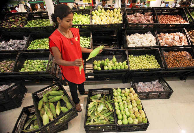 An employee arranges vegetables in the fresh foods section of a Reliance Fresh supermarket in Mumbai.