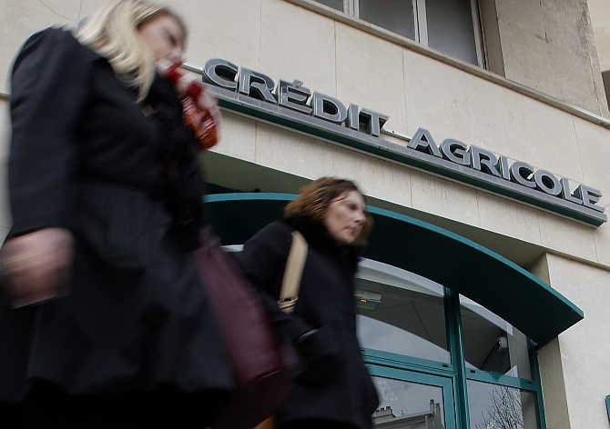 Passers-by walk in front of a branch of French bank Credit Agricole in Marseille, France.