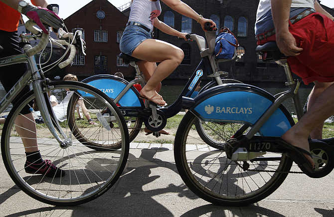 Cyclist ride bicycles sponsored by Barclays Bank at Camden Lock in London.