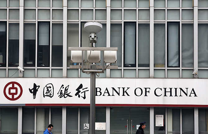 A security official and a man walk past a signboard of Bank of China at its branch in Beijing.