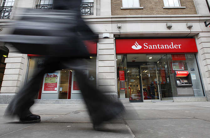 A pedestrian walks past a branch of a Santander bank in London.