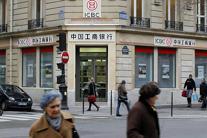 People walk past the entrance of the Industrial and Commercial Bank of China in Paris.