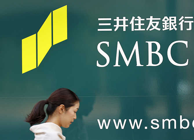 A woman walks past a signboard of Sumitomo Mitsui Banking Corporation in Tokyo.