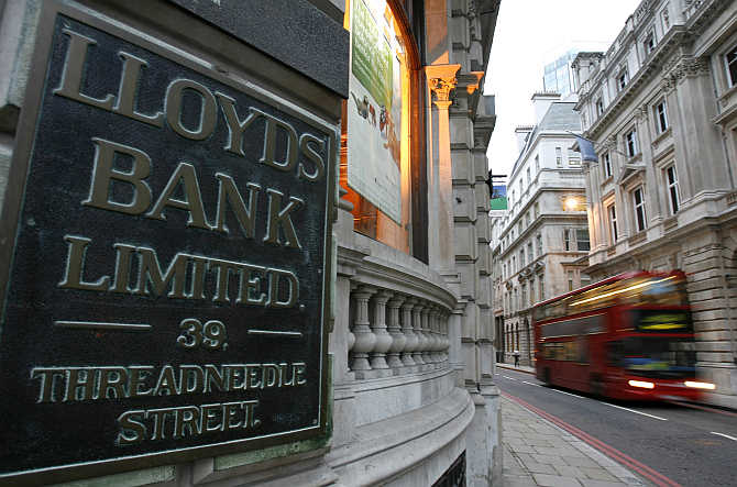 A bus passes a branch of Lloyds bank in the City of London.