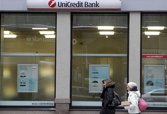 People walk past UniCredit Bank branch in Riga, Latvia.