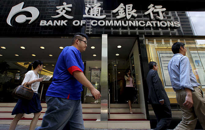 People walk past the Bank of Communications at its central branch in the financial district of Hong Kong.