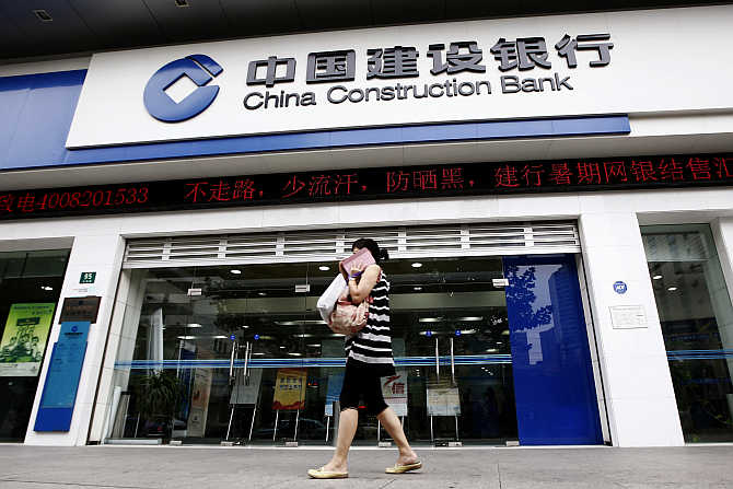 A woman walks past a branch of the China Construction Bank in Shanghai.