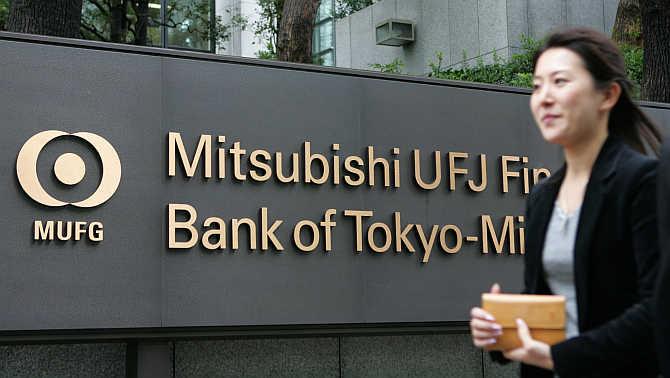 A woman walks past the headquarters of Bank of Tokyo-Mitsubishi UFJ in Tokyo.
