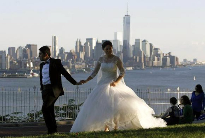 Mustafa Aktas from Ankara, Turkey holds hands with his bride Hatice Yigiter as they walk in front of the skyline of New York's Lower Manhattan and One World Trade Center in a park along the Hudson River in Weehawken, New Jersey.