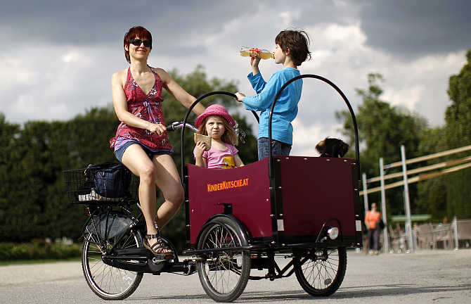 Christine Nouikat and her children Sophia, 4, and Niklas, 9, pose with their transport bicycle in a public park in Vienna, Austria.