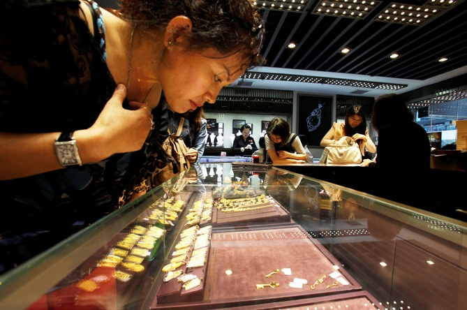 A customer looks at a few 24K gold keys left on an shelf inside a jewellery store.